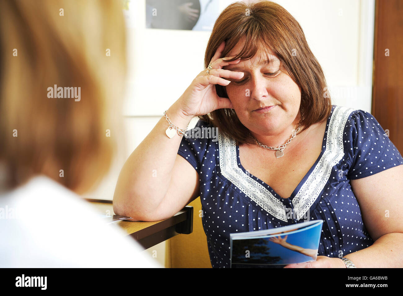 Overweight and obese woman reads a stop smoking leaflet during consultation with health advisor at NHS drop in centre - Stock Image