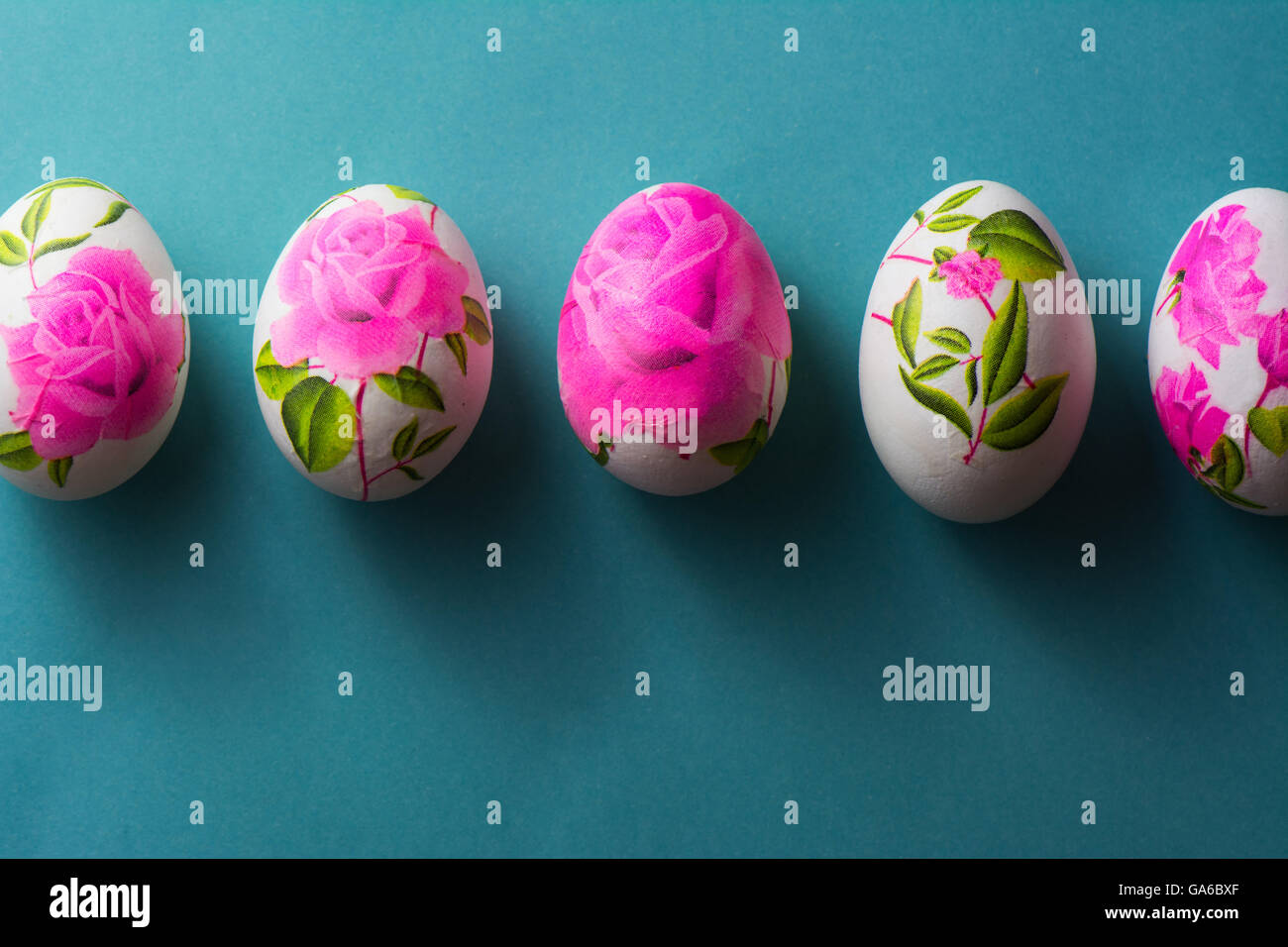 Decoupage easter eggs decorated with flowered paper napkins and decoupage easter eggs decorated with flowered paper napkins and stuck with glue om blue background above view mightylinksfo