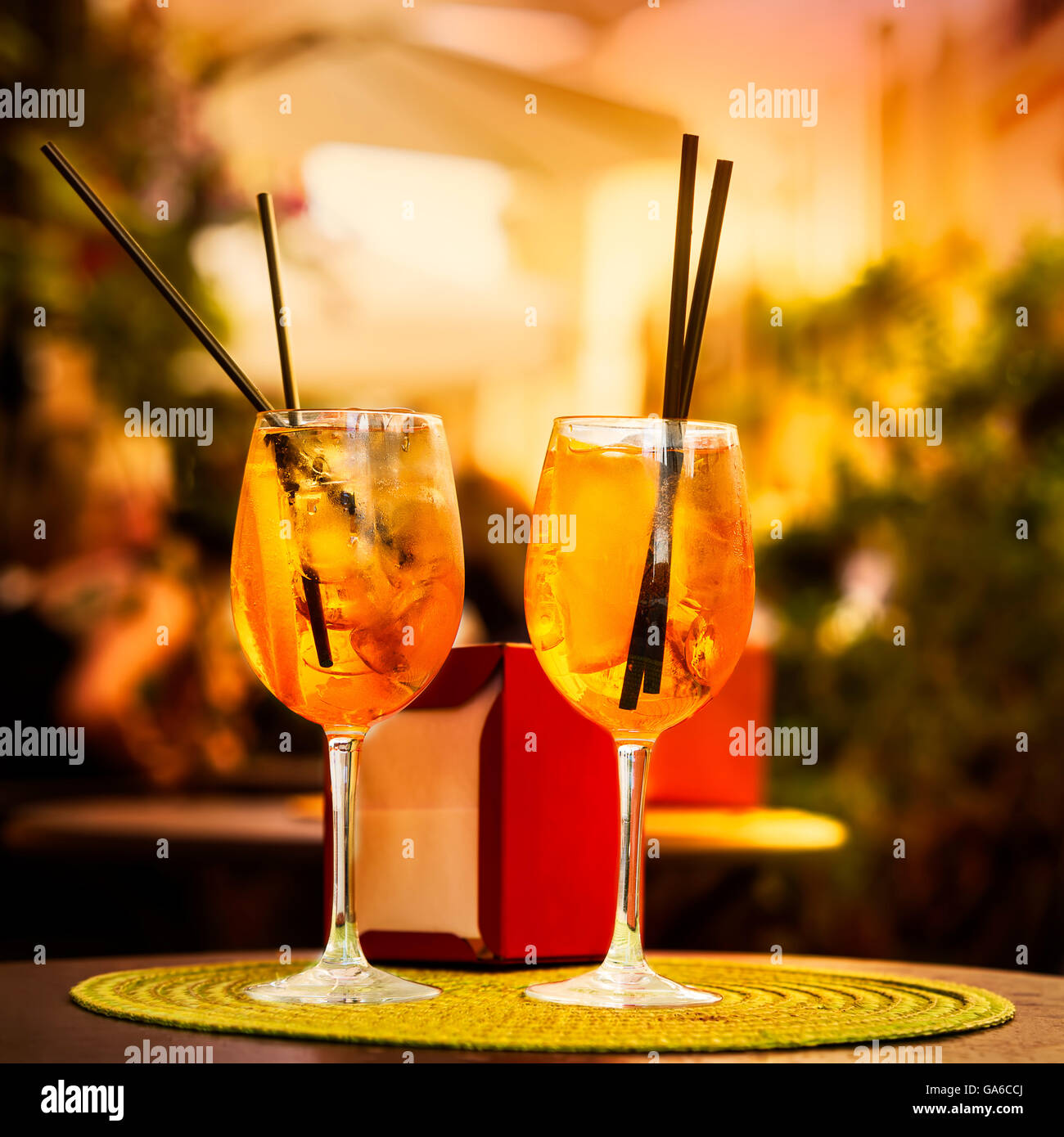 Aperol Spritz Cocktail. Alcoholic beverage based on table with ice cubes and oranges. - Stock Image