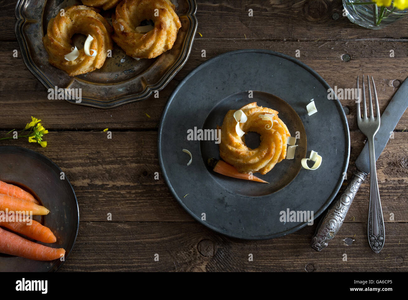 mini carrot cake with white chocolate on a rustic wooden table. - Stock Image