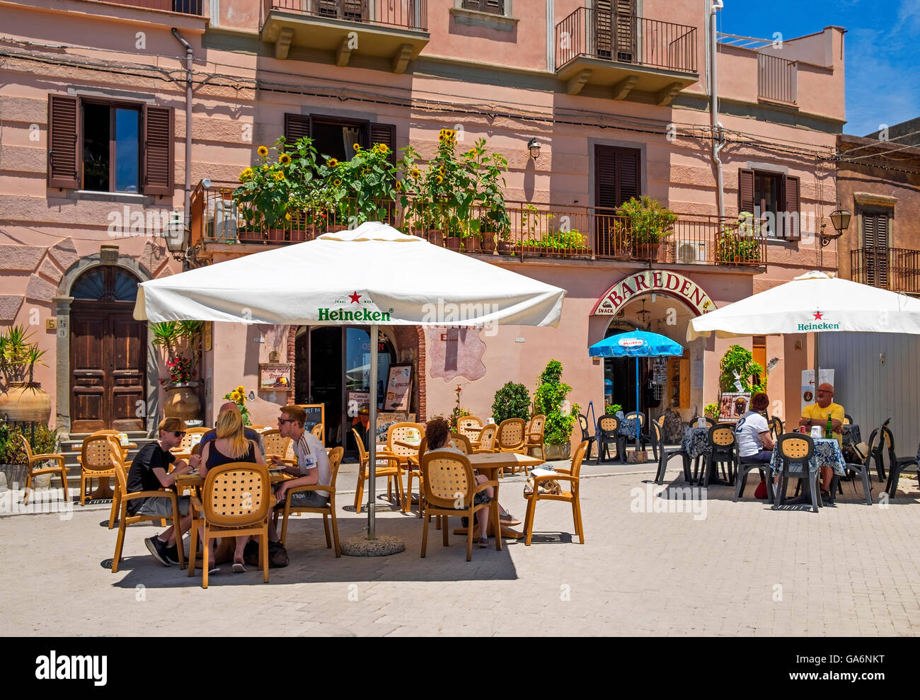 Visitors taking shade and refreshments in the village square of Forza D'Agro, Sicily, Italy - Stock Image
