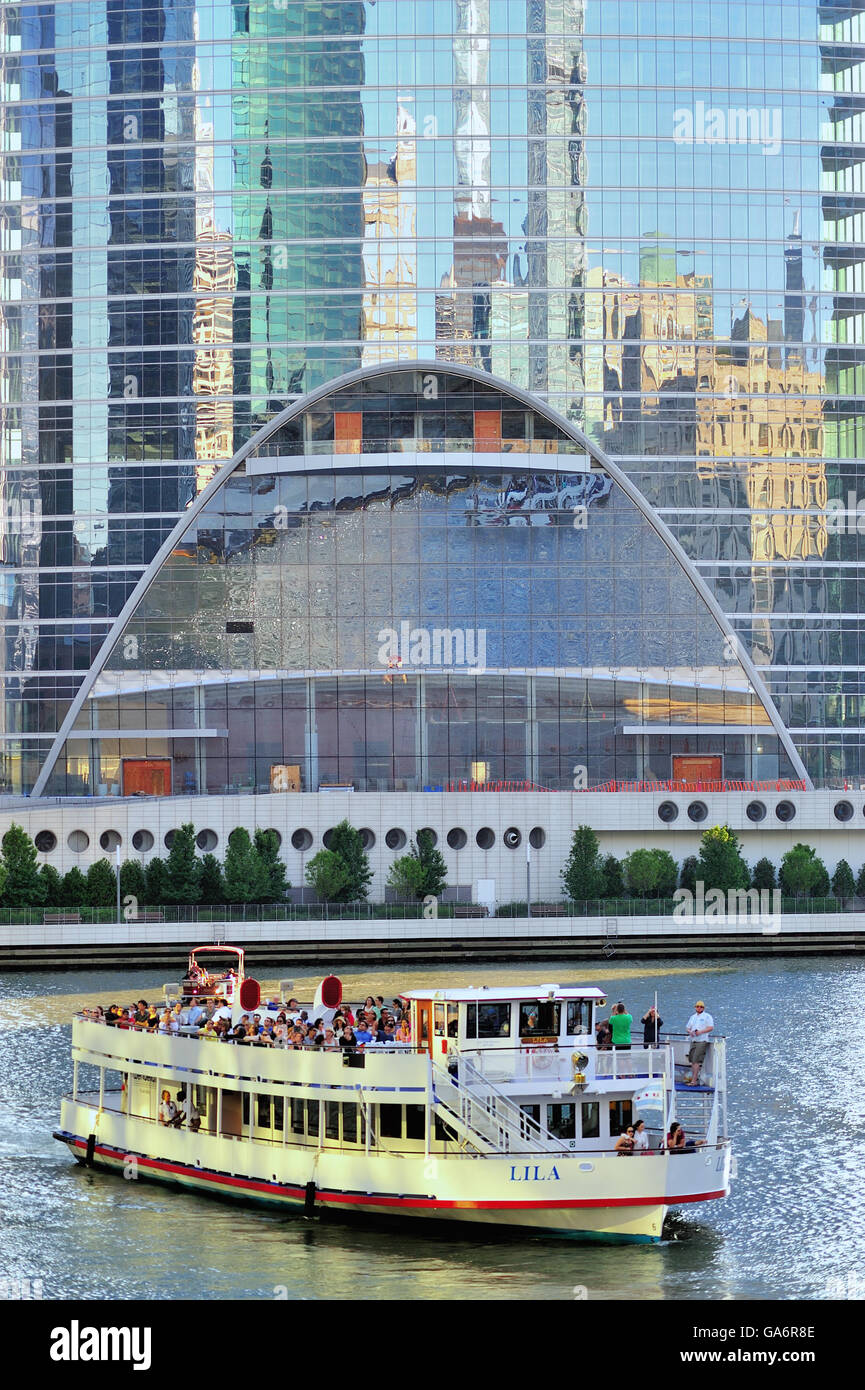 A tourist boat traveling on the Chicago River is reflected in the glass of the under construction River Point project. - Stock Image