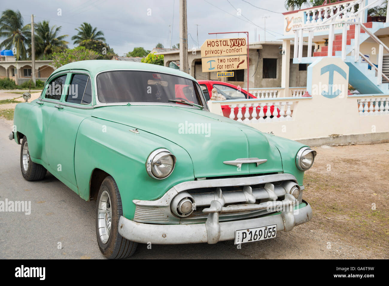 Vintage Chevy taxi parked outside a family-run hostel with rooms for rent to tourists in Playa Larga, Cuba. - Stock Image
