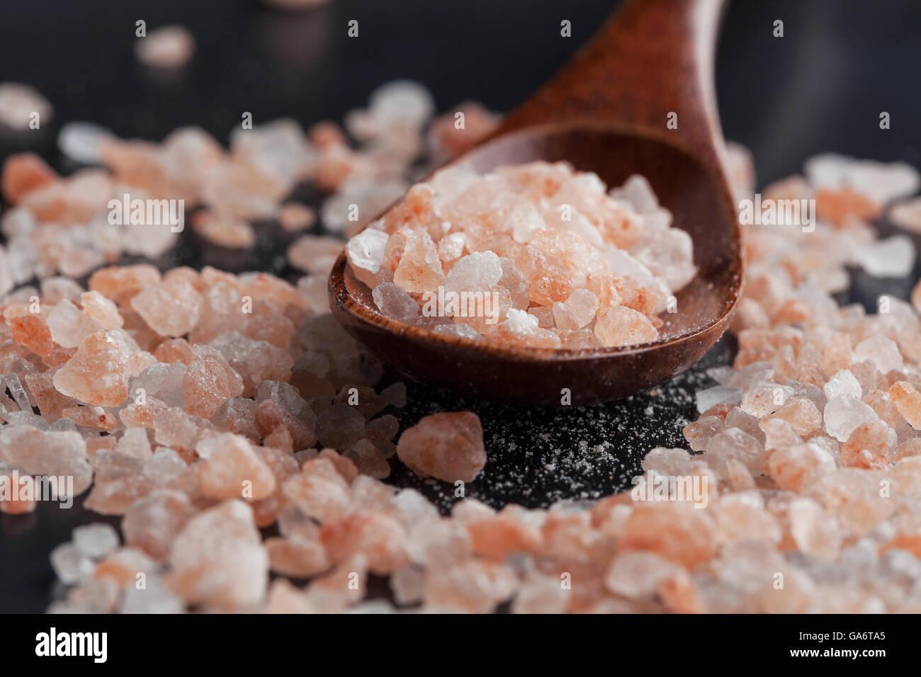 Himalayan pink rock salt in wooden spoon closeup - Stock Image