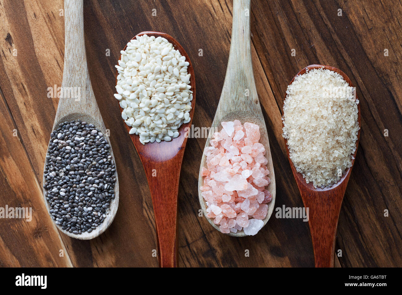 Himalayan pink salt, raw cane sugar, sesame and black Chia seeds in wooden spoons, top view - Stock Image