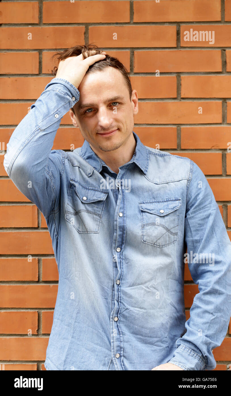 handsome young man in a blue denim shirt - Stock Image
