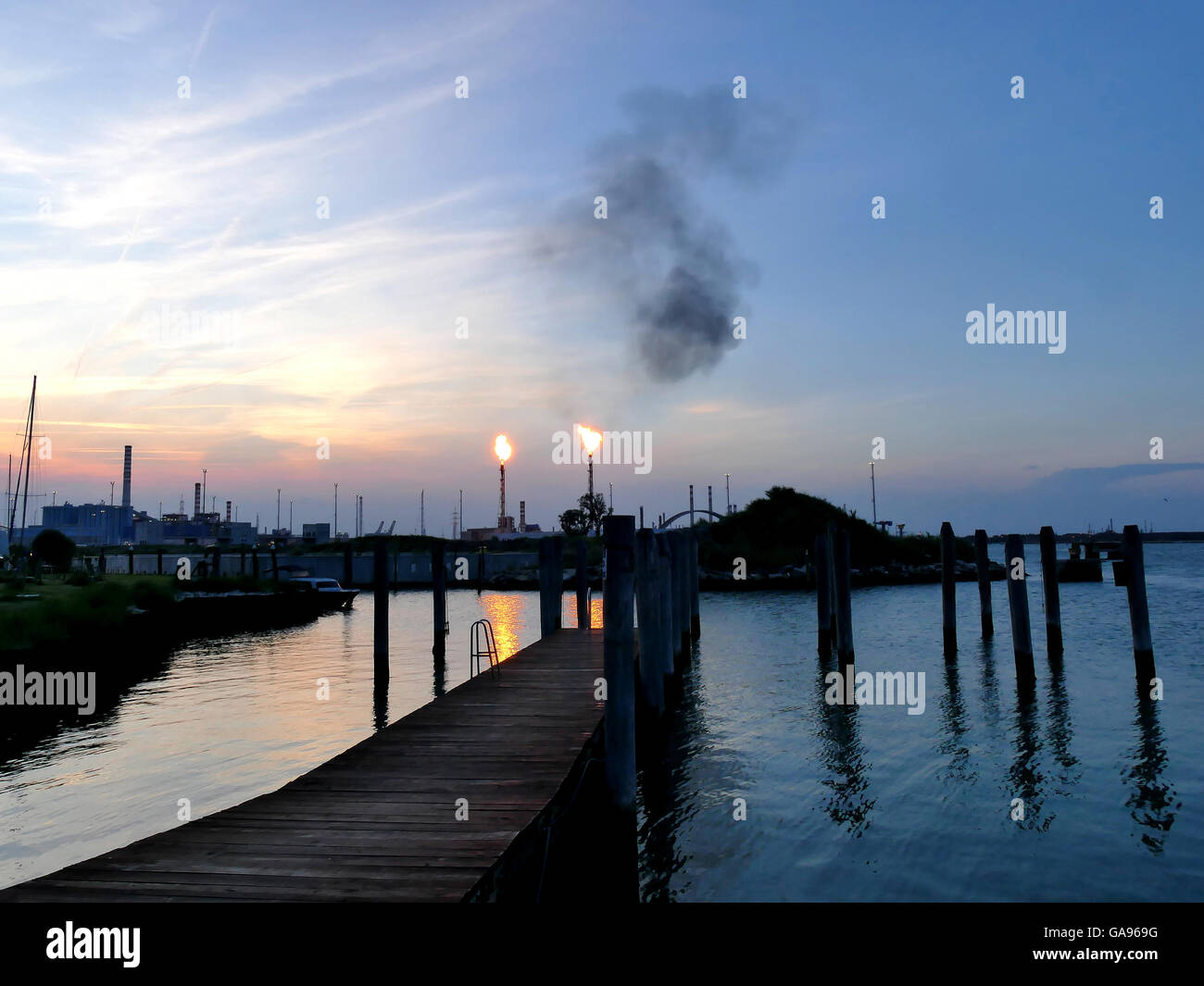 Oil refinery bursting flames at sunset close to shore, Venice Italy - Stock Image