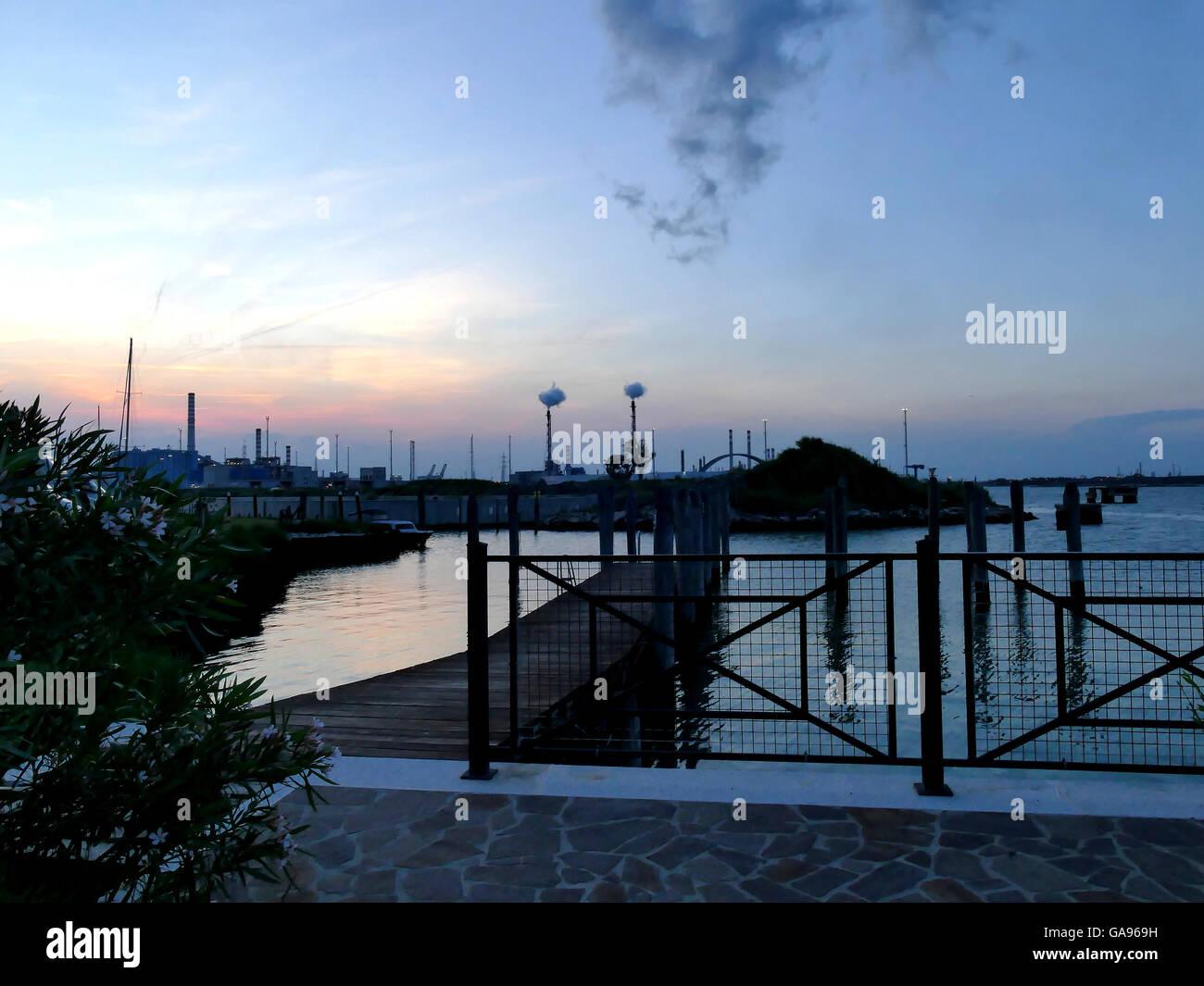 Oil refinery bursting smoke at sunset close to shore, Venice Italy - Stock Image