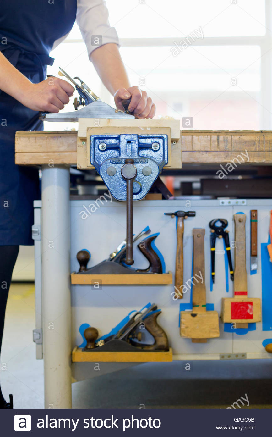 high school student using wood plane tool on workbench in