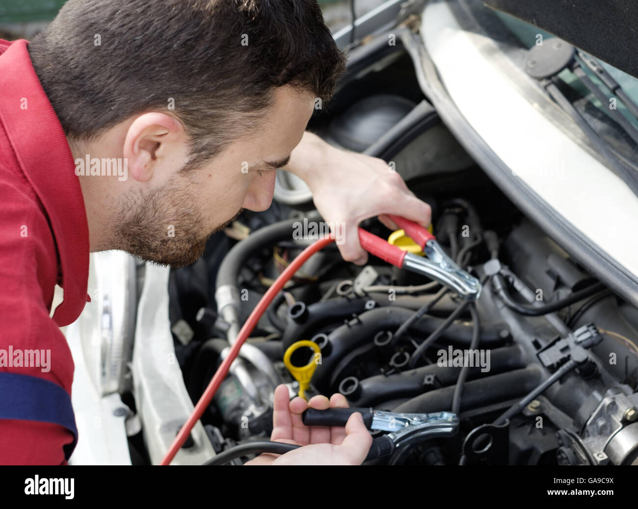 mechanic working on car engine with electricity cables - Stock Image