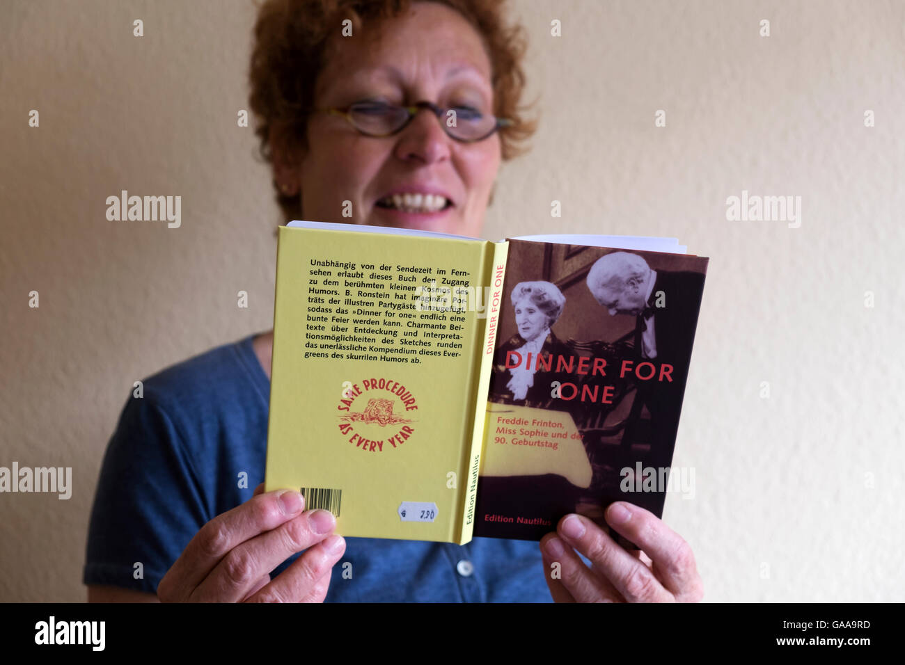 German woman reading a book about the famous Dinner For One TV drama which is shown in Germany ever year on New - Stock Image