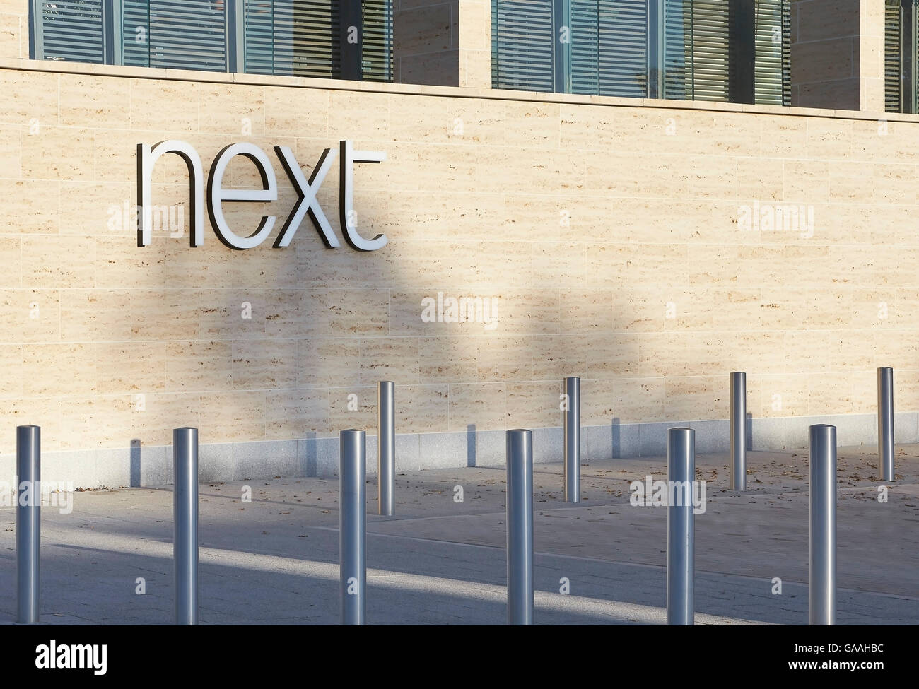 Detail of facade with company logo. Next -  Home and Garden Stores, Southampton, United Kingdom. Architect: Stanton - Stock Image