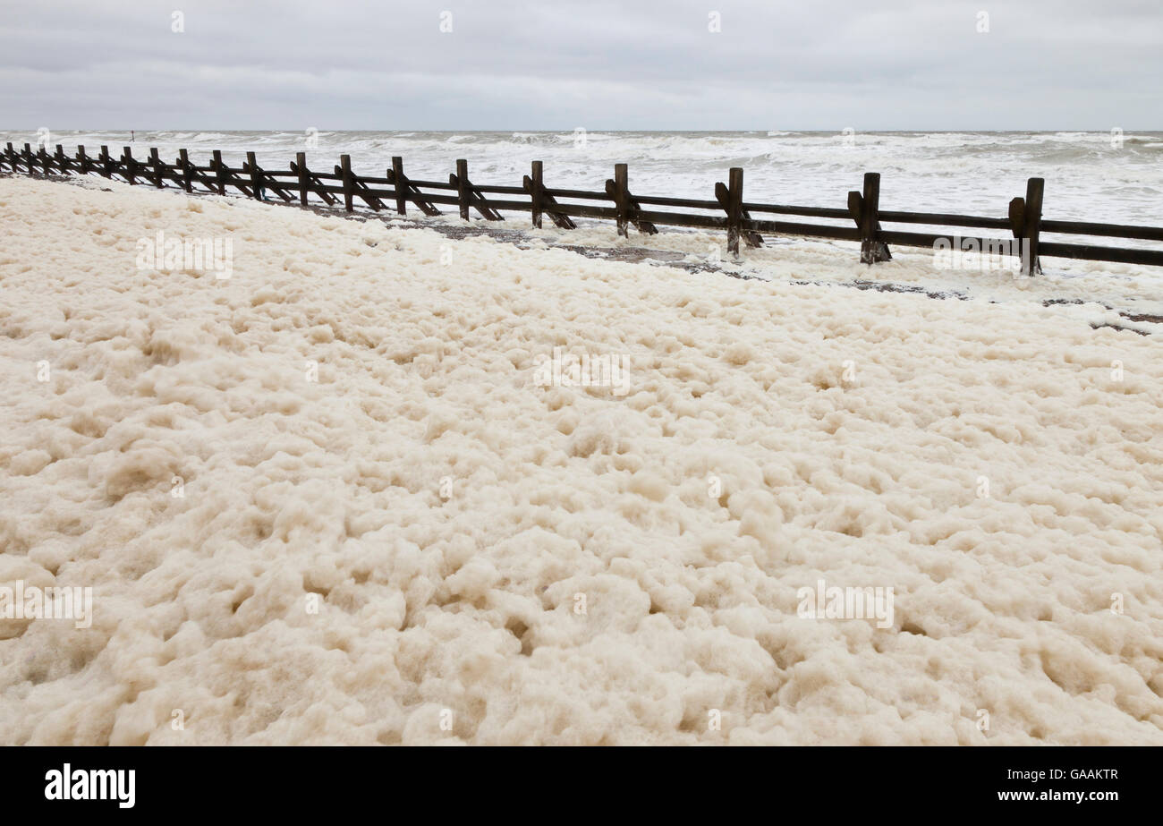West Runton with spume along the shoreline at high tide in north Norfolk, England, UK - Stock Image
