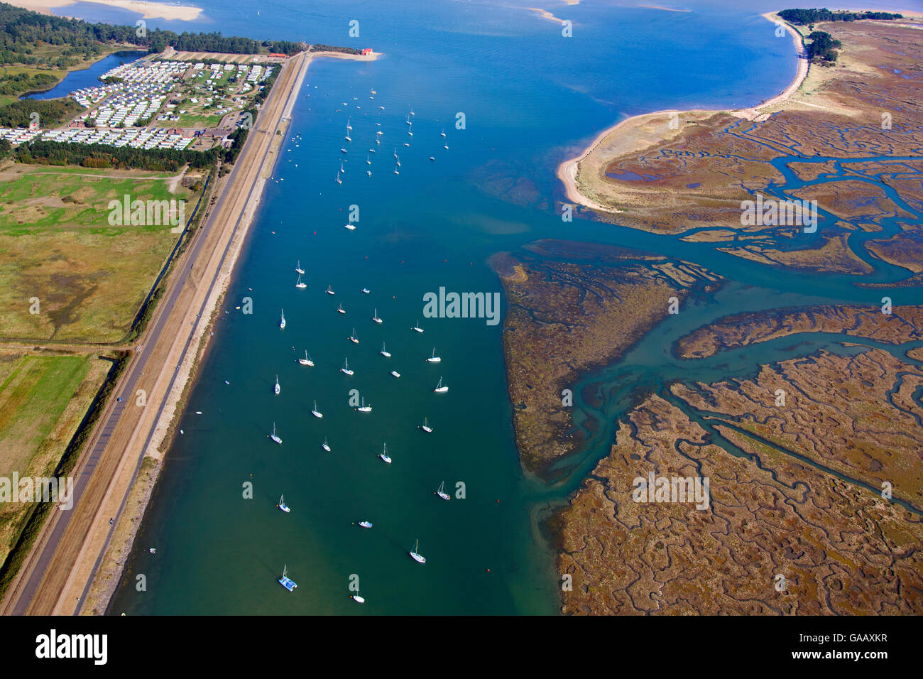 Aerial view of  boats in East Fleet, with Pinewoods caravan park, and salt marshes on the coast of Norfolk, England, - Stock Image