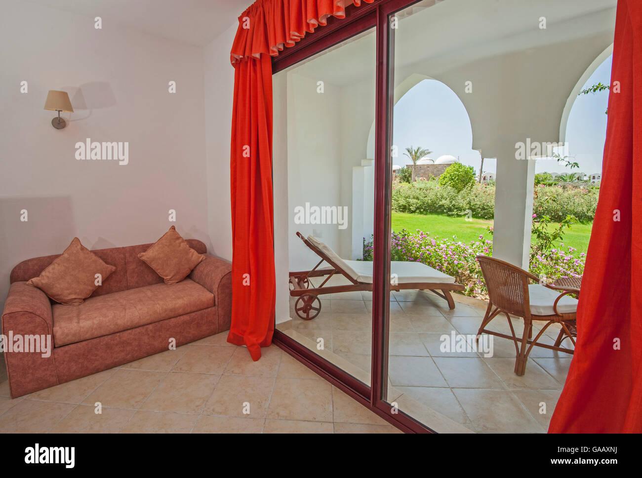 interior design of a luxury tropical hotel resort bedroom with balcony patio area