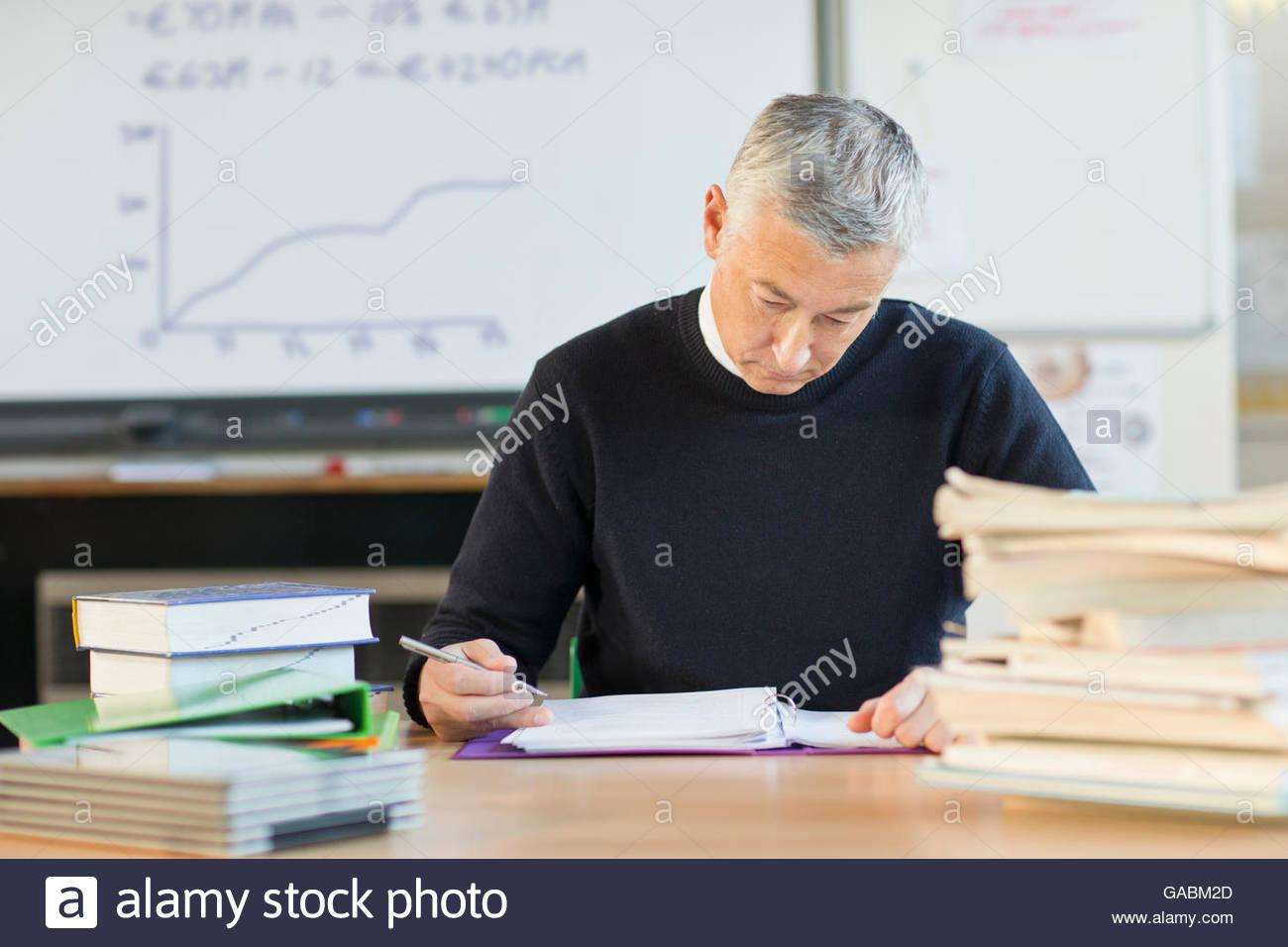 Teacher grading homework in classroom - Stock Image