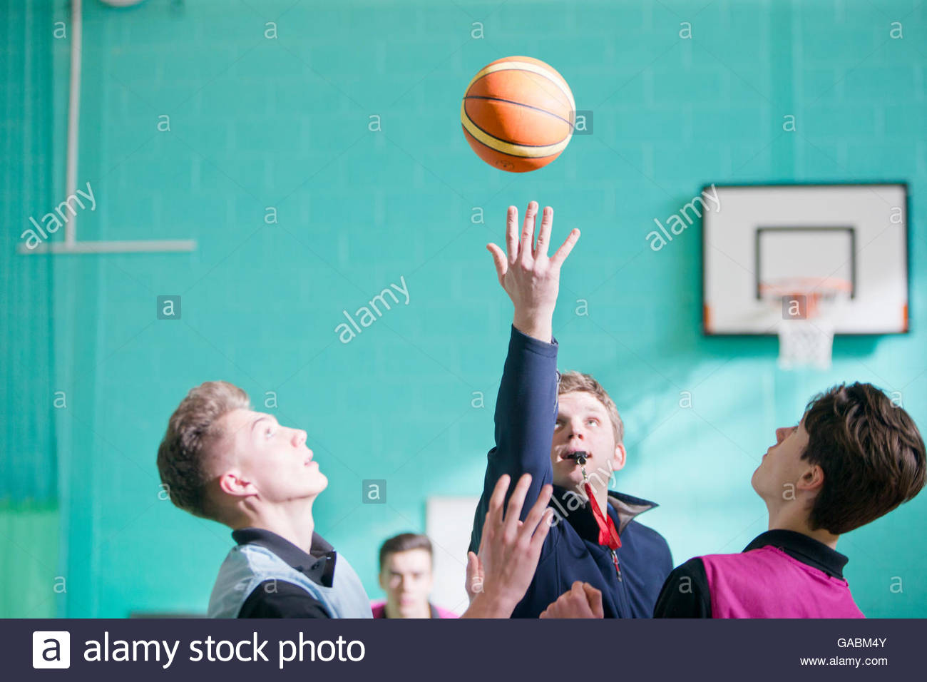 Gym teacher starting high school basketball game with tip off - Stock Image