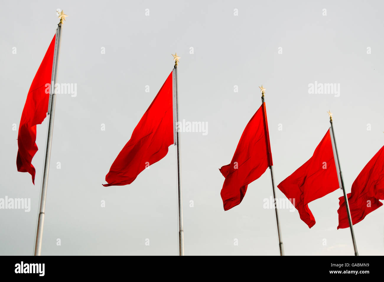 Chinese flags on a cloudy grey sky in Beijing, China - Stock Image
