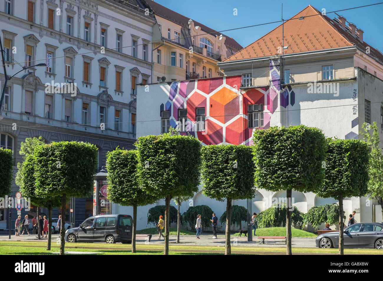 Street art, comprising building mural and clipped trees, on Karoly Krt, Budapest, Hungary - Stock Image