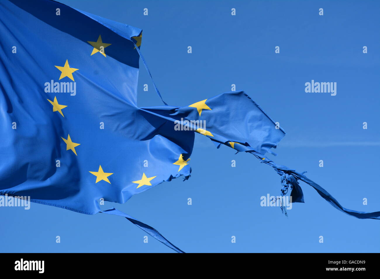 The european union twelve star flag torn and with knots in the wind on blue sky - Stock Image
