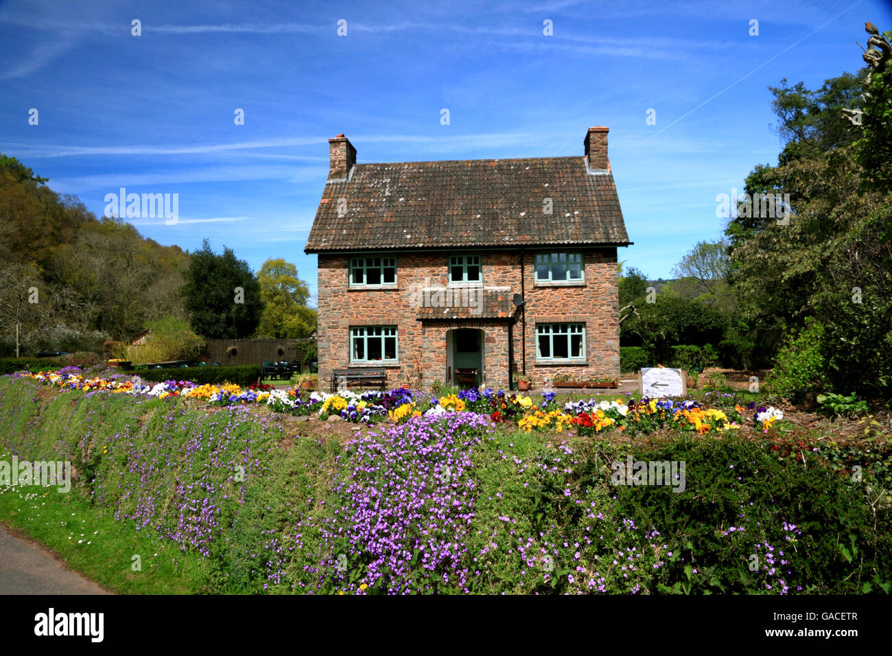 A square cottage with a flower filled garden. - Stock Image