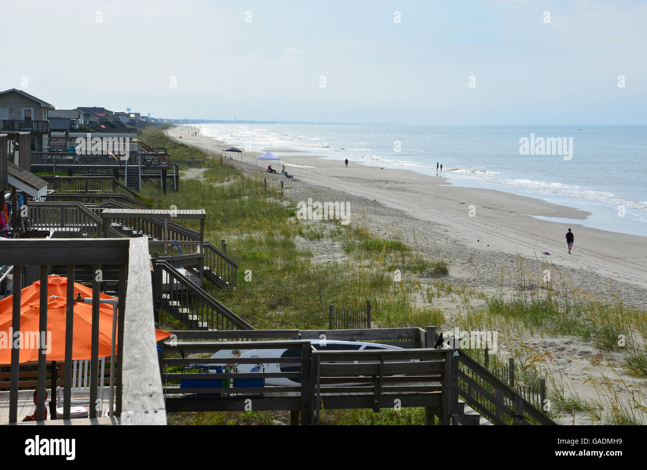 Figures walk and run on the sand at Long Beach, Oak Island NC, early in the morning. - Stock Image