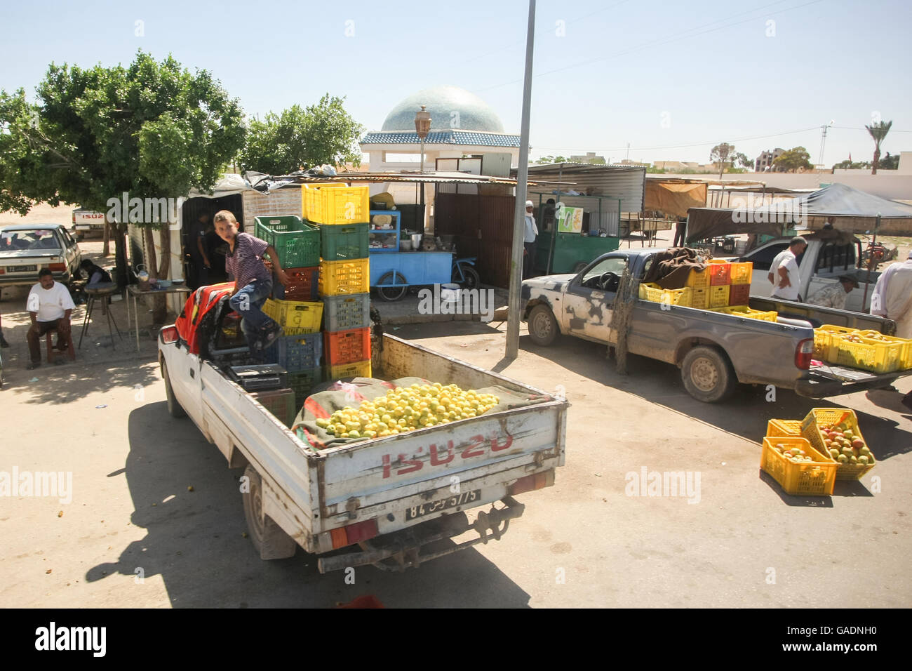 People packing groceries on pick up trucks at food market in