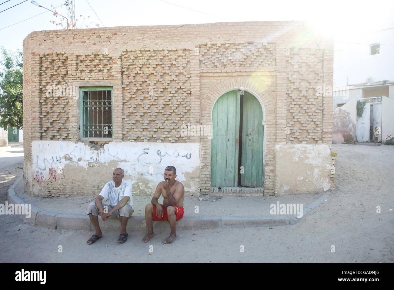 TOZEUR, TUNISIA - SEPTEMBER 16, 2012 : Two tunisian men sitting on the pavement in front of the house in Tozeur, Stock Photo