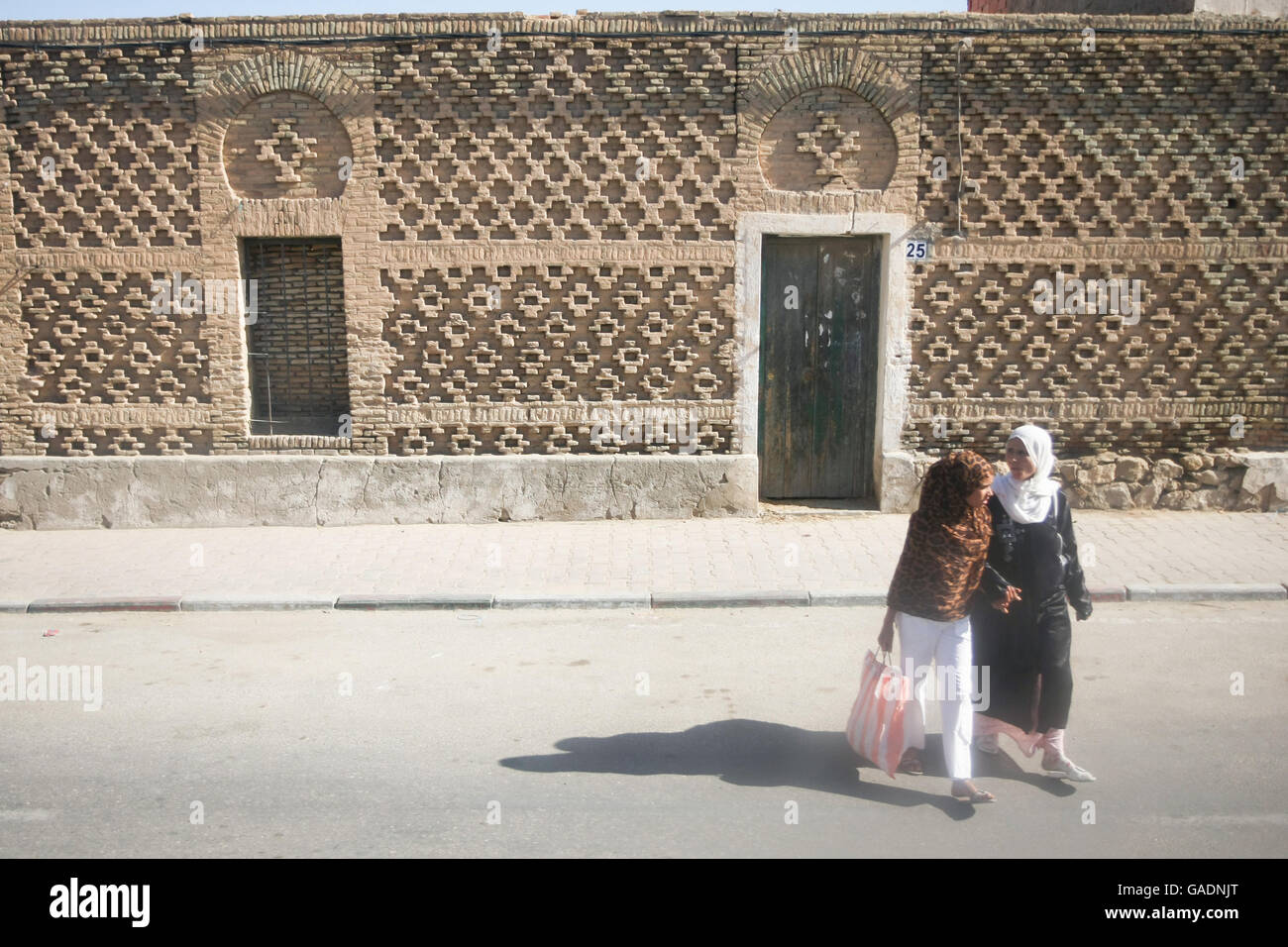 TOZEUR, TUNISIA - SEPTEMBER 16, 2012 : Two tunisian women crossing the street in Tozeur, Tunisia. Stock Photo