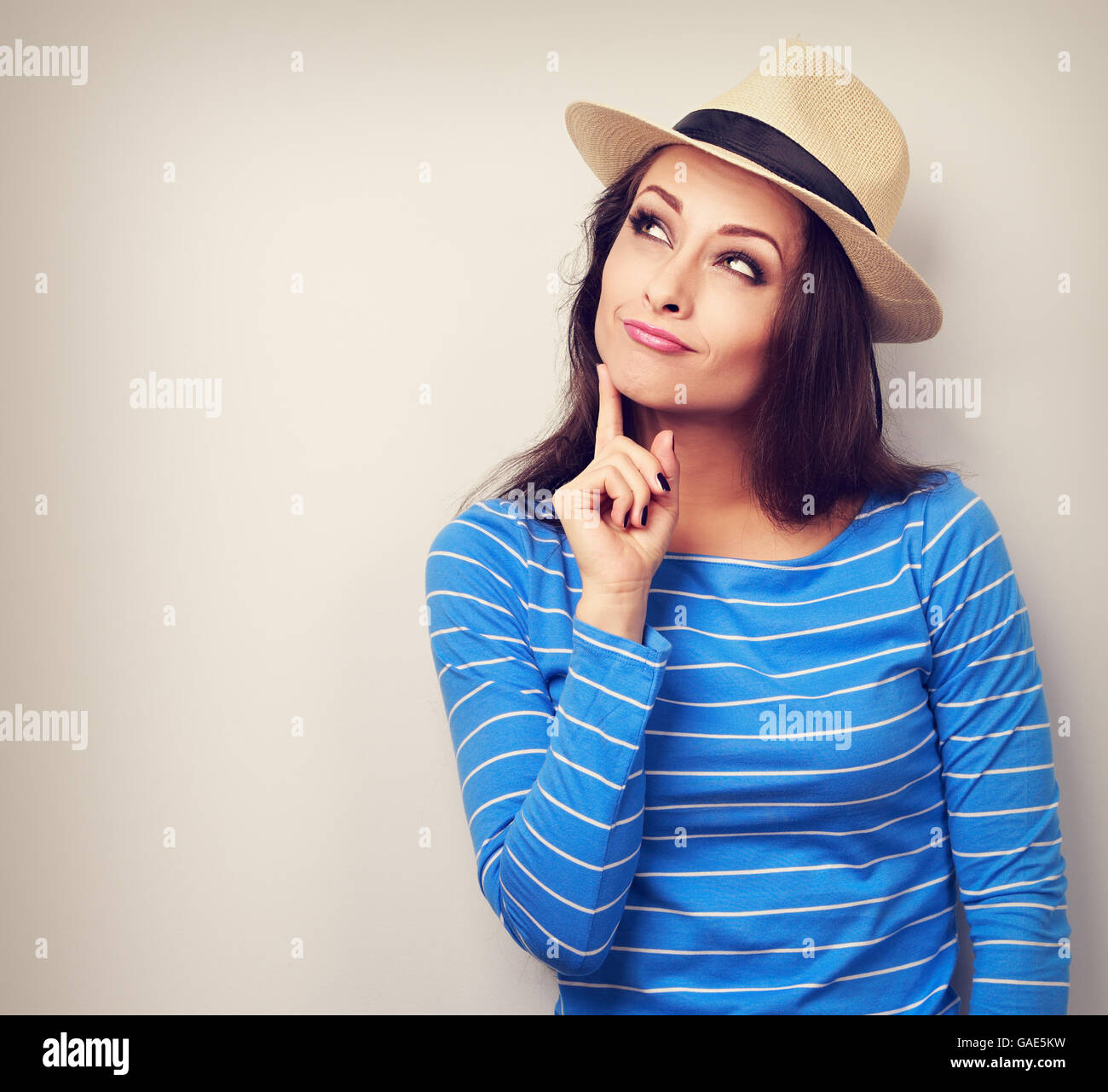 Grimacing young lady in summer hat thinking and looking up. Vintage toned portrait Stock Photo