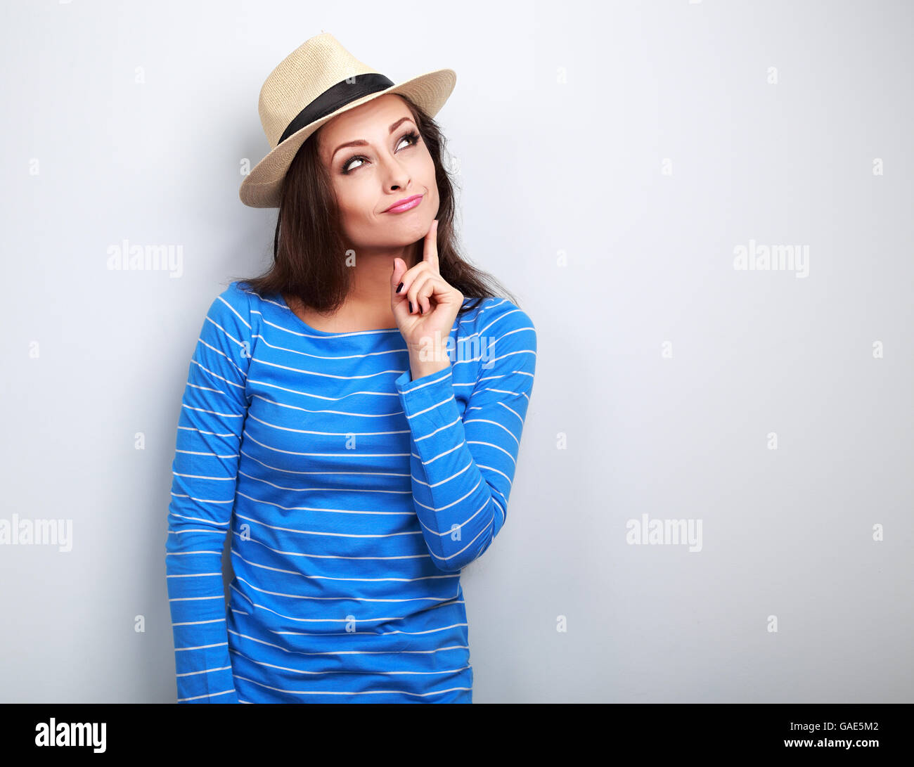 Grimacing young lady in summer hat thinking and looking up on blue background - Stock Image