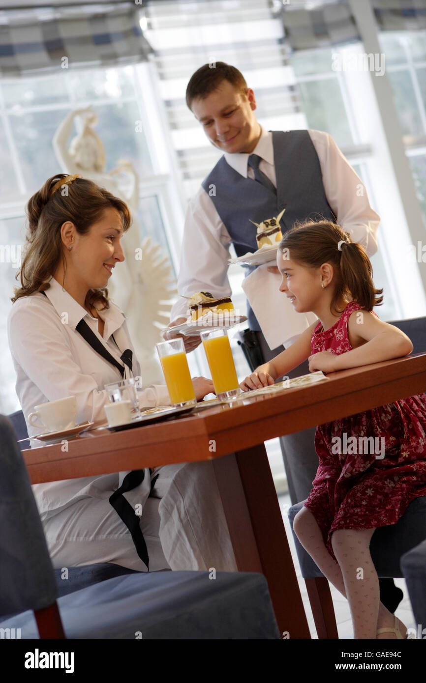 Waiter serving coffee and cake to a mother and her daughter in a café - Stock Image