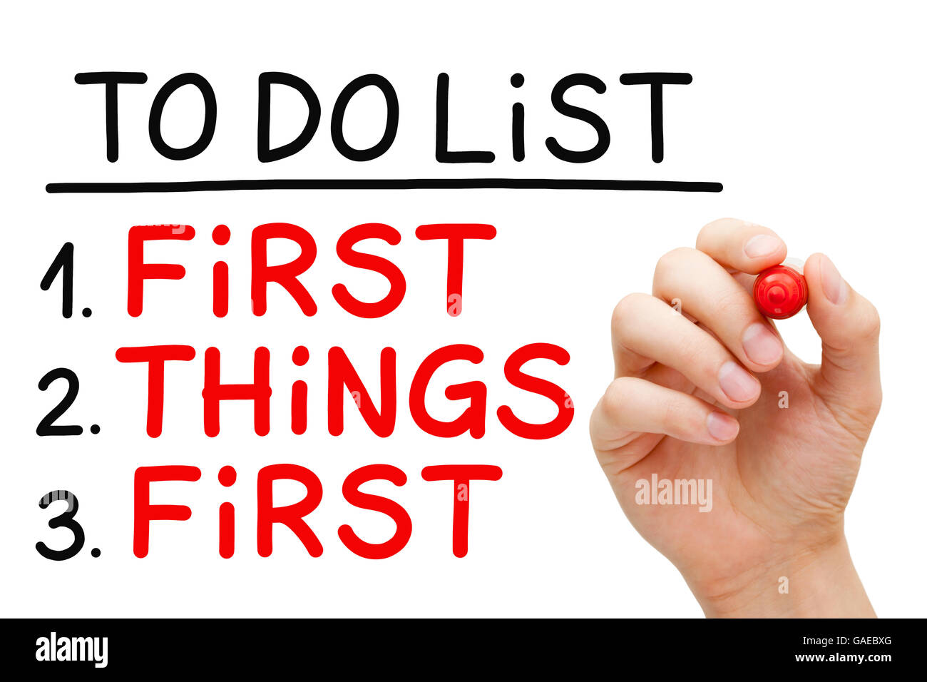 Hand writing First Things First in To Do List with red marker isolated on white. - Stock Image