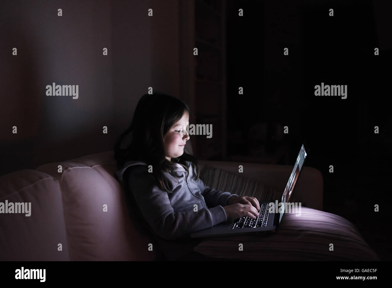 Little girl, sitting in a dark, playing with laptop - Stock Image