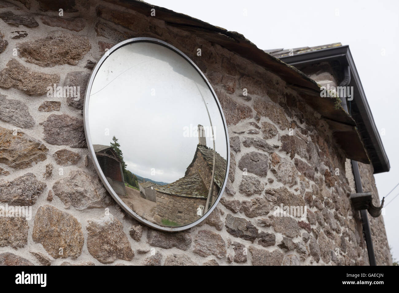 O Hospital, Spain: Convex traffic mirror at a narrow intersection in the village. - Stock Image