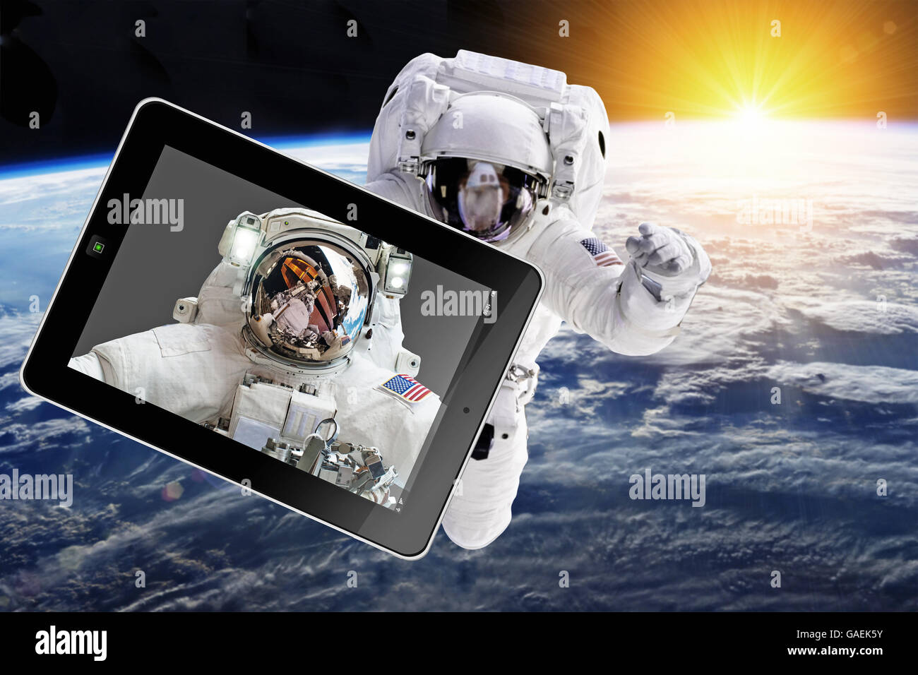 Astronaut in outer space with tablet - Elements of this image furnished by NASA - Stock Image