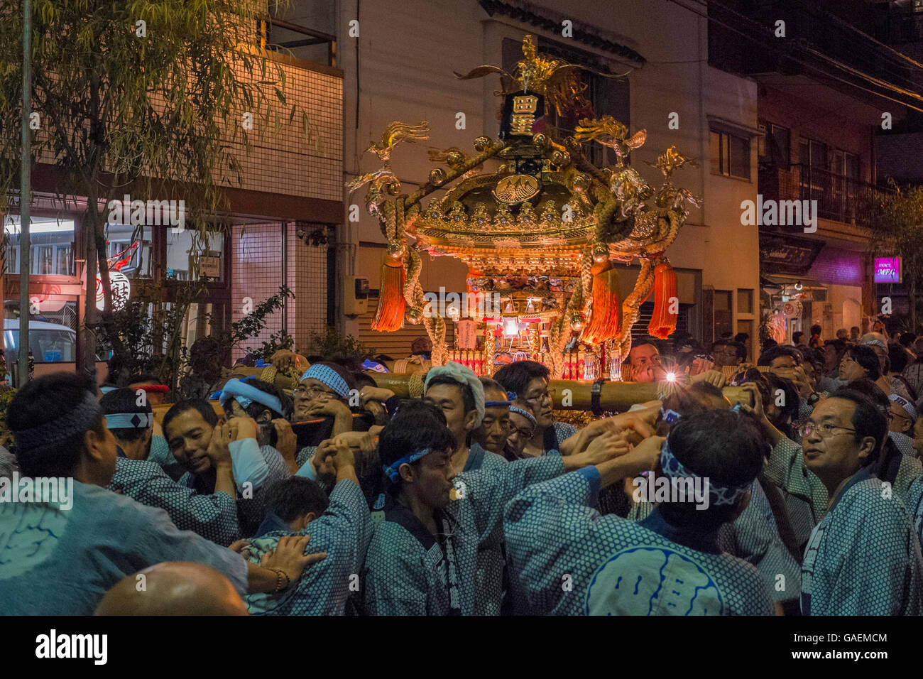 People carrying a shrine at night in the annual festival in Tokyo - Stock Image