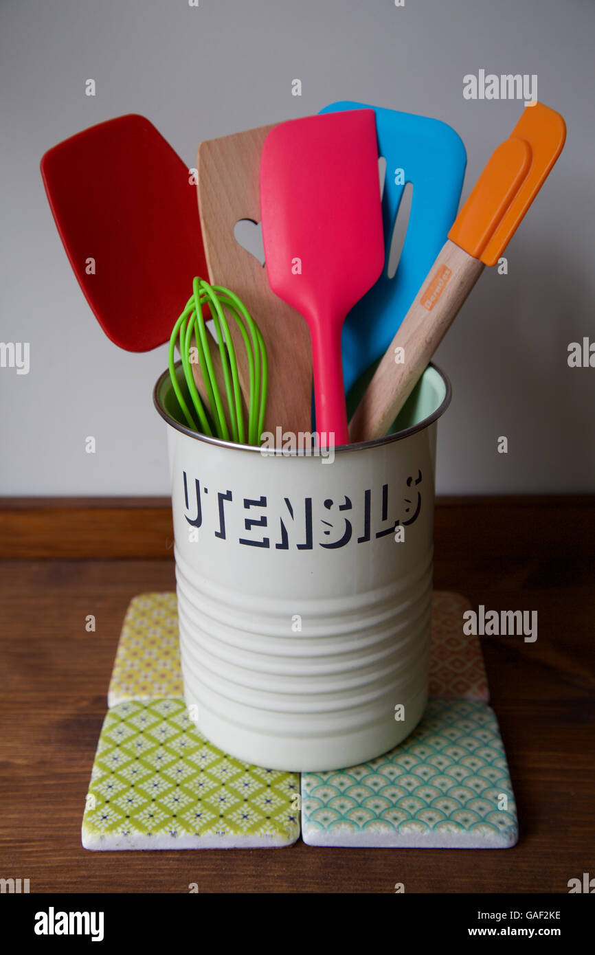 Retro kitchen utensils pot on wooden counter and tiles with six bright and colourful baking spatula whisk and spoons - Stock Image