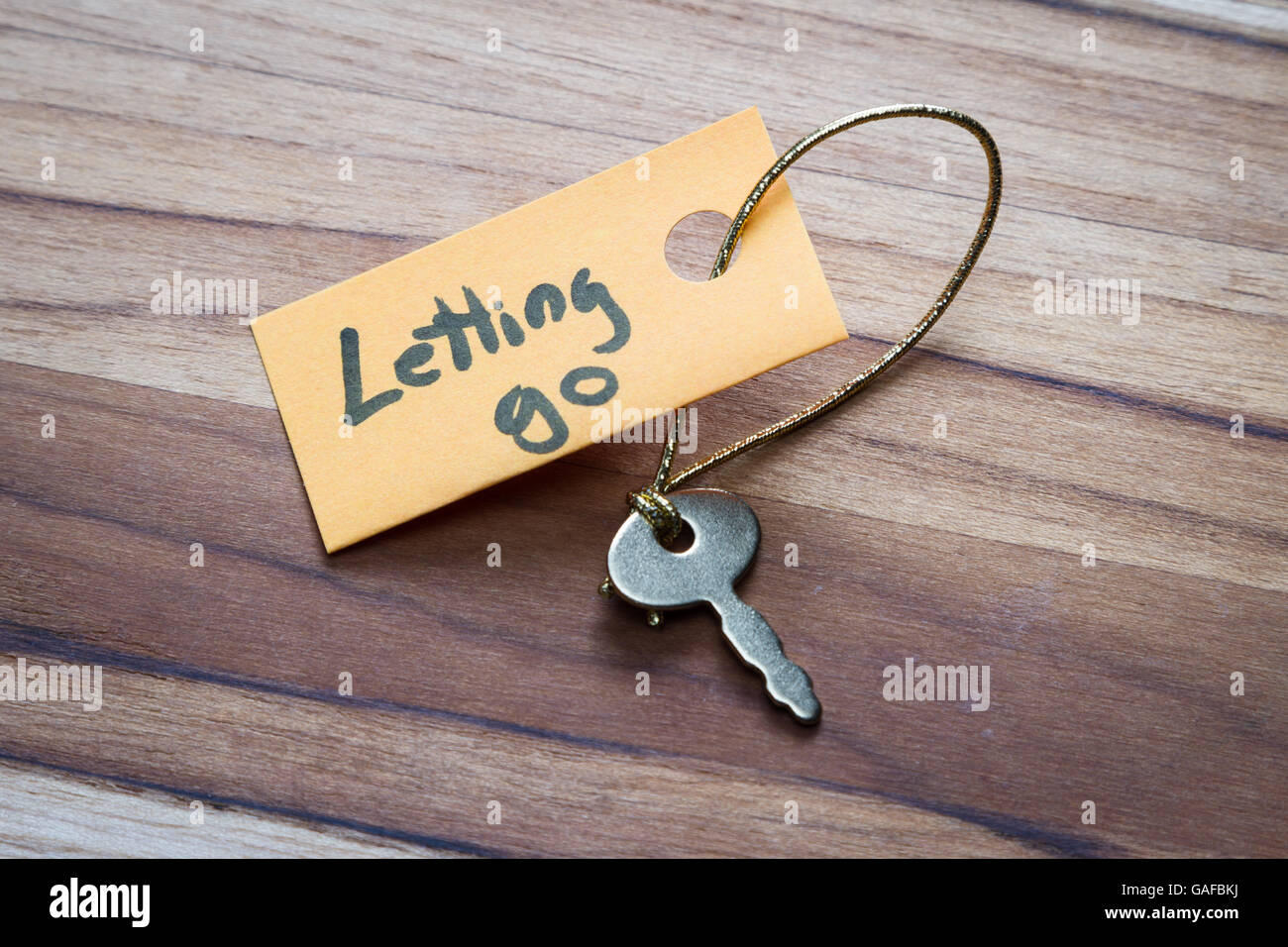 concept for a happy life using an old decorative key and a hand written tag attached by a golden cord - Stock Image