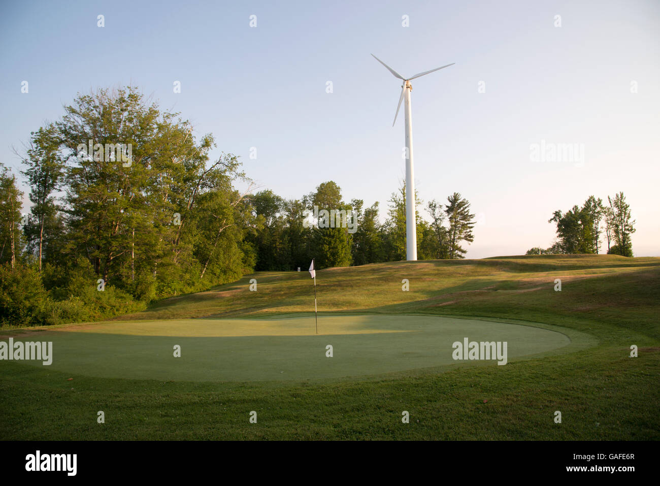 Wind turbine behind golf green in the White Mountain region of northern New Hampshire, early morning, summer time - Stock Image