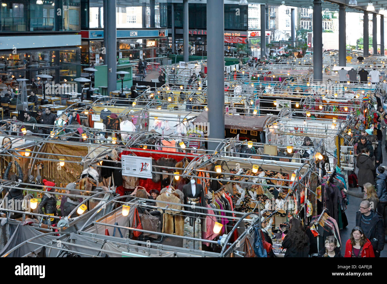 Interior view looking down from above on people shopping at stalls in the The Old Spitalfields covered indoor market - Stock Image