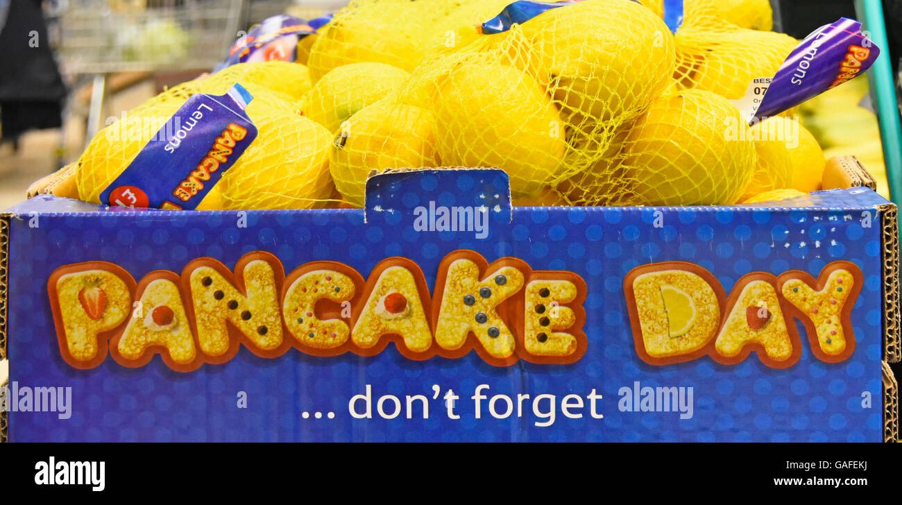 Supermarket food store shopping promotion and display of Pancake Day lemons being sold in string bags England UK - Stock Image