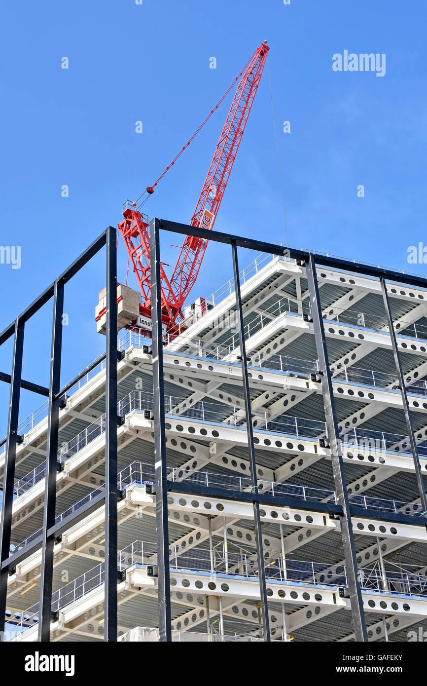 Crane on building construction site  steel framed building with preformed holes in beams facilitate installation - Stock Image