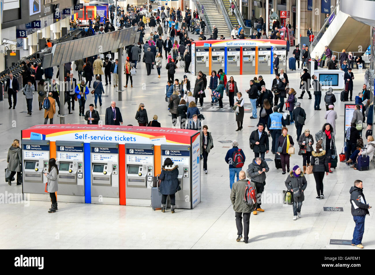 Looking down on passengers & commuters and Self Service ticket machines at Waterloo train Station London England - Stock Image