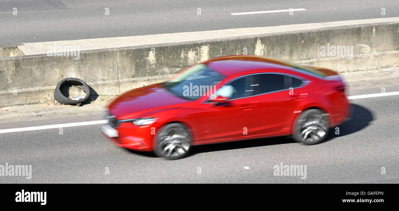 Damaged burst tyre propped up against central concrete crash barrier beside lane 4 of UK M25 motorway with fast - Stock Image