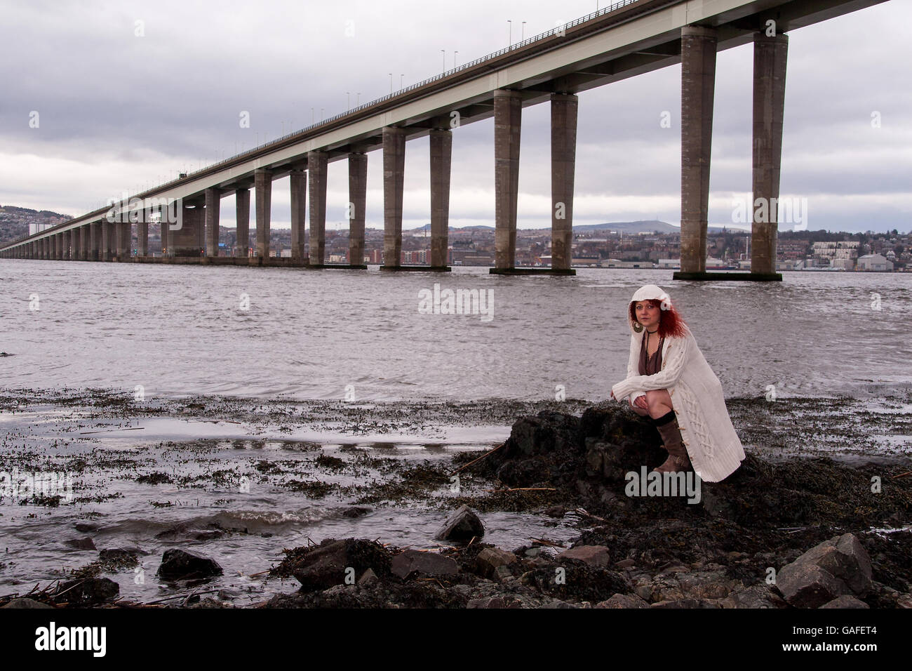 A woman crouched down along the Firth of Tay coastline on a very blustery day with her hair being blown by the wind Stock Photo