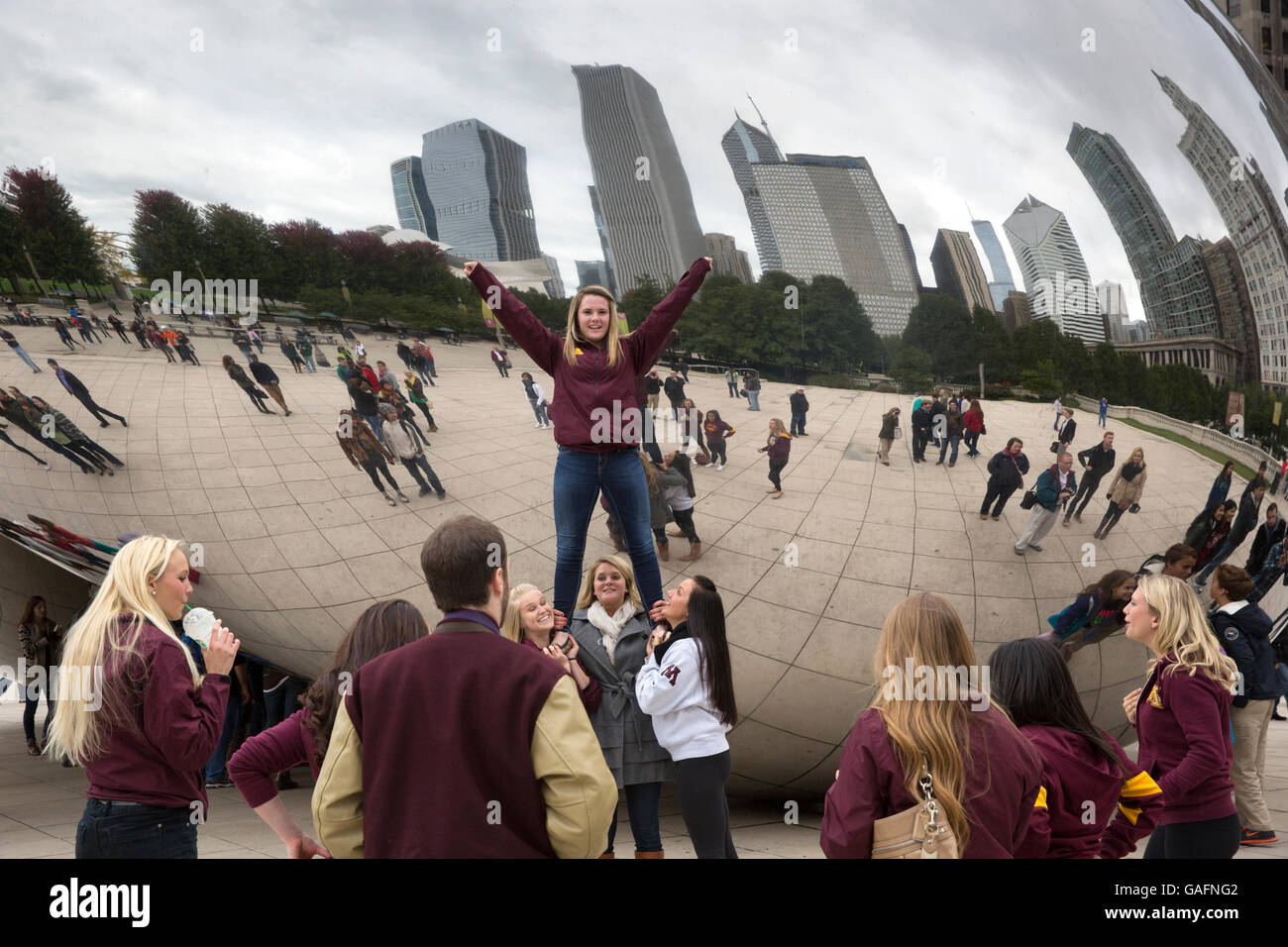University of Minnesota cheerleaders in the front the Cloud Gate sculpture in Chicago, Illinois. - Stock Image