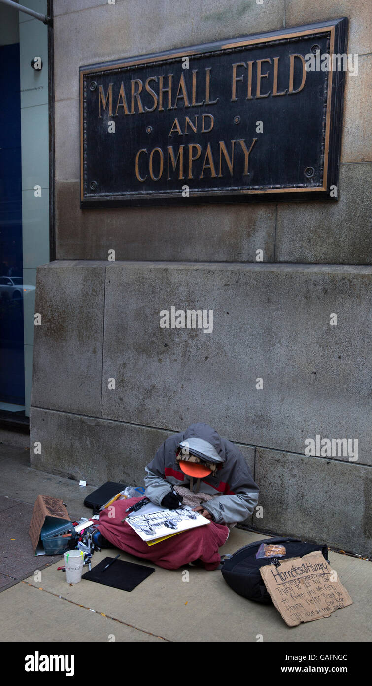 Homeless and hungry person making art for sale in downtown Chicago, Illinois - Stock Image