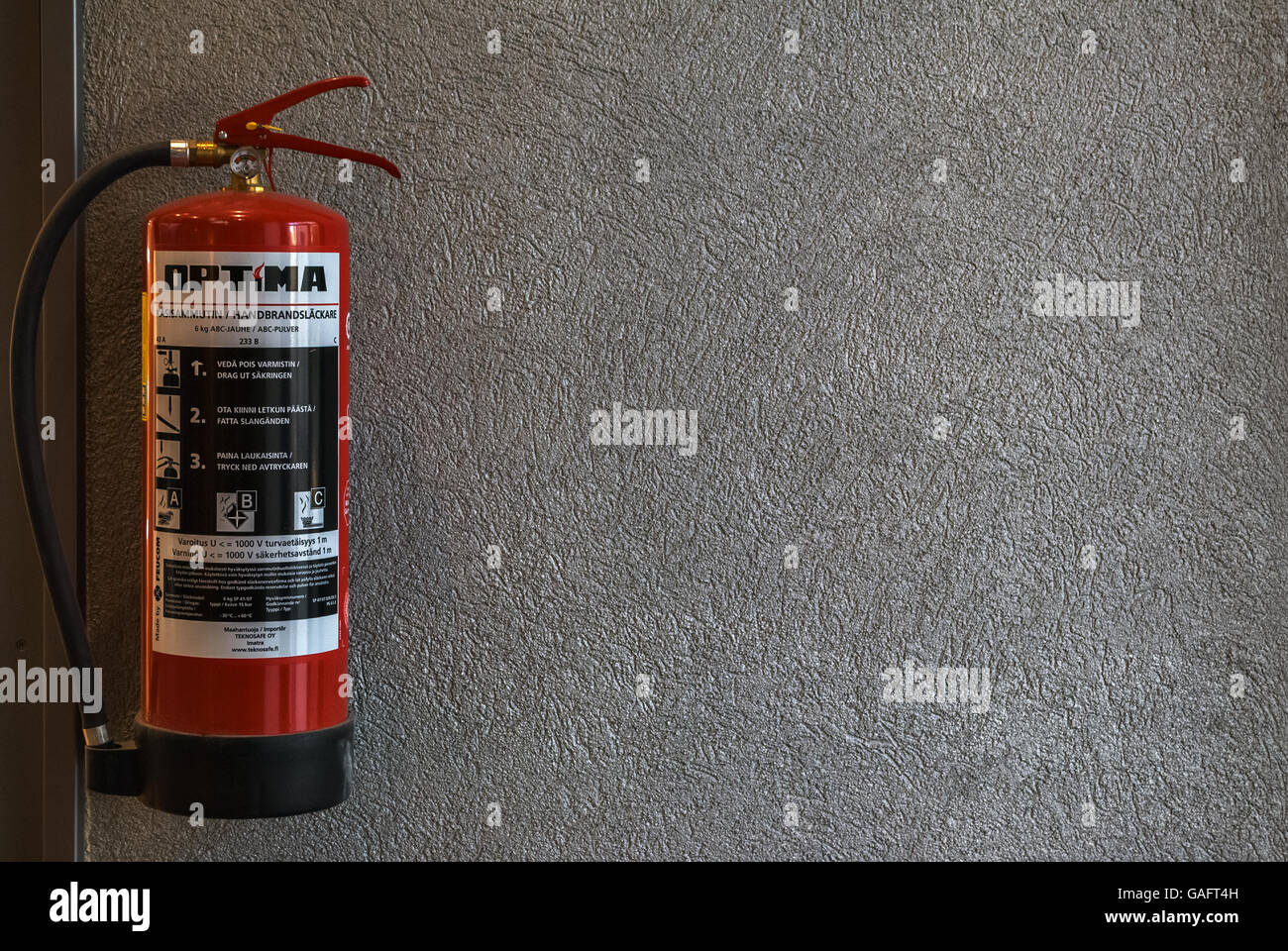 Red fire extinguisher hanging on the wall inside a shopping complex in the city of Lappeenranta, Finland. - Stock Image