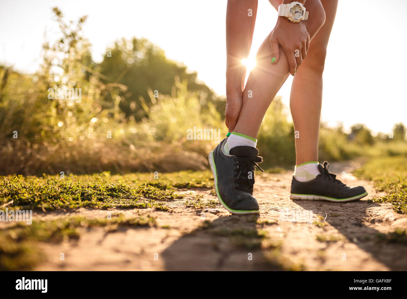 woman runner hold her sports injured leg - Stock Image